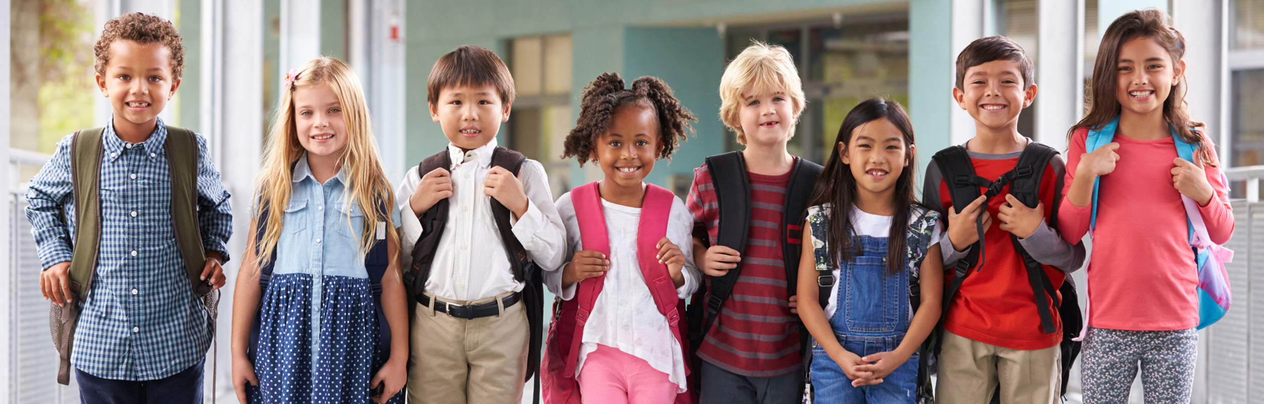 Students standing in a line with backpacks