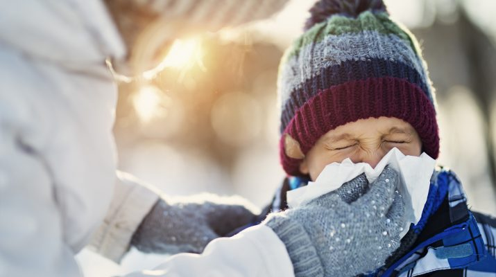 Parent assisting student in blowing his nose while outside in the snow